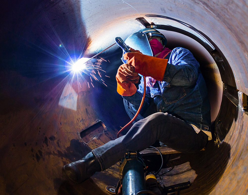 welder working inside a large pipe
